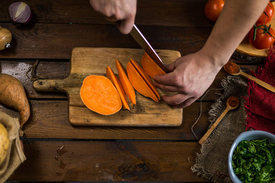 Raw sweet potatoes cutting on cutting board on wooden background top view