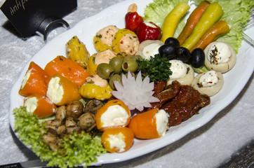 Antipasti-Teller, angerichtet mit getrockneten Tomaten, gefüllter Paprika, gefüllten Pilzen und Oliven an Salat