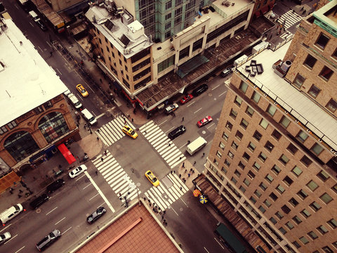Bird's eye view of New York City. Looking down on Manhattan from skyscraper. Cars, taxis and people moving through busy intersection.  White zebra crossing and New York yellow cabs. Filter effect.