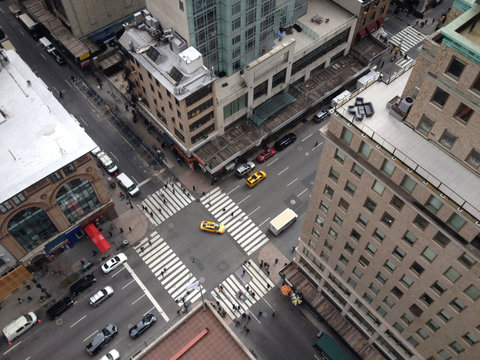 Looking down on New York Street from above in tall Manhattan skyscraper.  Bird's eye view of midtown Manhattan street 5th Avenue. Yellow taxis driving down New York City street. People crossing street