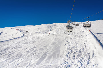 Skiers on the chairlift in high mountains during sunny day. Winter season