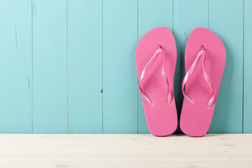 Pink flip flops on wooden background