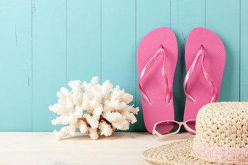 Summer vacation beach background with flip flops, coral and straw hat