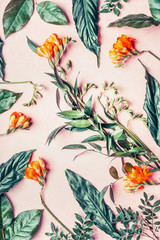 Wall Mural - Creative flat lay made of tropical flowers and leaves on pastel pink background, top view