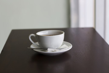 Fresh coffee in white cup on wooden table