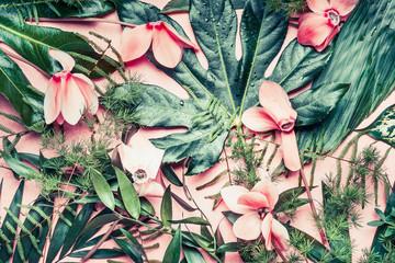 Twórczy układ wykonane z tropikalnych kwiatów i liści palmowych na pastelowym tle różowy, widok z góry, płaskie świeckich