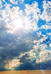 Bright blue sky, sun and fluffy beautiful clouds. Nature background, wallpaper.