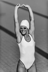 Female swimmer streching on poolside