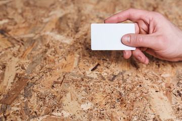 Man's hand is holding a business card on wooden background