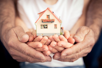Family holding house in hands