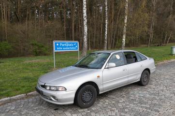Illegal entsorgtes Altauto auf einem Autobahnparkplatz
