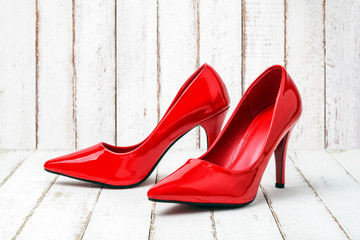 Red stiletto on wood background