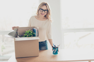 Concept of promotion at work. Portrait of attractive woman in spectacles unpacking her belongings at new office and putting stand for pens on the table
