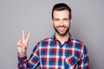 A horizontal portrait of young bearded man showing v-sign against gray background