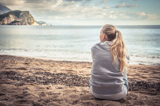 Pensive lonely young woman sitting on beach hugging her knees and looking into the distance with hope
