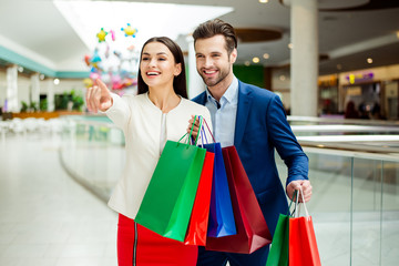 It's shopping time with  sales and fun. Cute cheerful  successful happy lovely couple in jacket holding colored shopping bags, pointing on shop  and laughing in mall at holiday