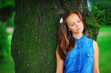 Cute young elegant girl with eyes closed leaning against a centuries-old tree, enjoying holiday. The concept of unity of man with nature.