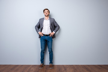 Full-length photo of successful handsome young man in formal wear smiling while  standing near gray wall