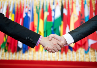 Businessmen shaking hands in front of the multi - national flag.    international business