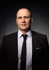 Confident businessman in black wearing suit and tie