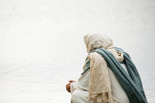 Jesus kneeling in prayer next to a body of water