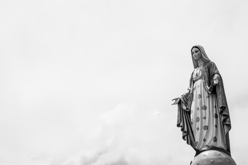 Statues of Holy Women on cloudy sky background