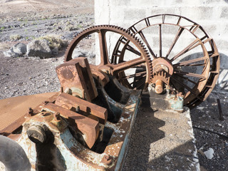 Rusty historic water pump in the dessert for agricultural means.