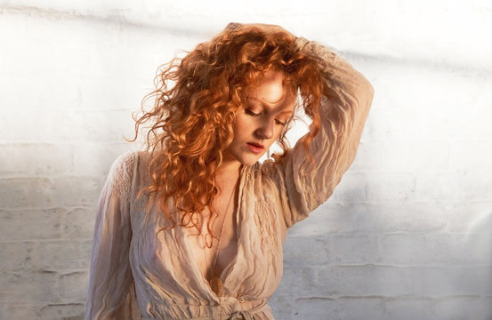 Portrait of beautiful young woman with long red hair and sultry look