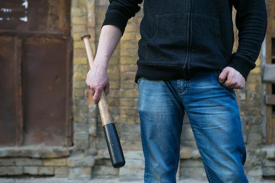 agressive street hooligan is holding a baseball bat
