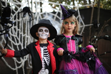 Trick-or-treating kids on Halloween patch. Boy in a Halloween costume of skeleton with hat and smocking and a girl with witch costume.