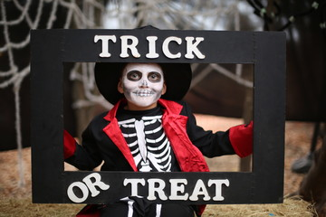 Boy in a costume of skeleton holding Trick or treat frame during Halloween patch