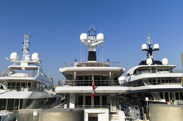 Modern yachts with massiv radar navigation systems at the stern at a jetty against blue skies