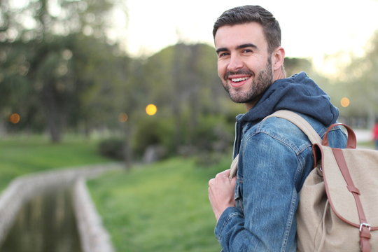 Smiley male holding backpack outdoors with copy space