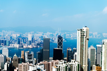 Hong Kong cityscape with victoria harbour and large group of tall buildings.