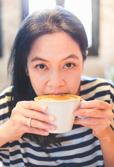 Close up face of asian woman sip hot cappuccino coffee in cafe shop,drinking hot beverage