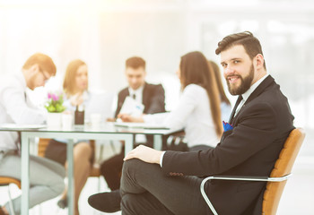 Manager of the company on the background of the working meeting the business team