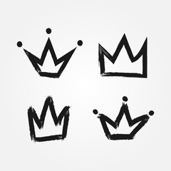 Set of silhouettes of crowns. Painted by hand with a rough brush. Isolated black icons.