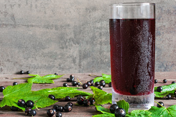 glass of cold black currant juice with fresh berries