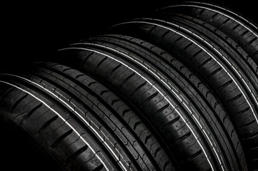 Car tires in row isolated on black