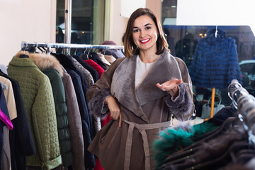 Woman trying on sheepskin coat in women's cloths store