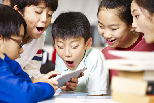 group of asian primary school pupil playing game using tablet
