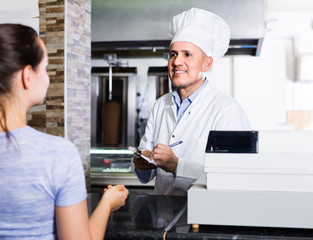 mature man cook taking order from customer on counter in fast food restaurant