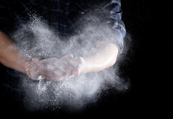 Chef hand clap with splash of white flour and black background
