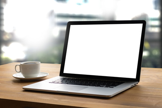 Laptop with blank screen on table interior, man at his workplace using technology