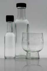 Bottiglie e bicchiere riflessi.