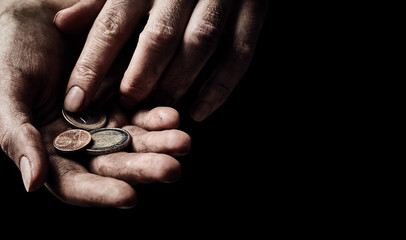 Hands of beggar with few coins