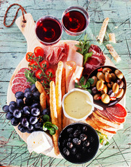 Mediterranean variety food ingredients  with ham, salami, baked olives, bread sticks,brie,tomatoes  for snacks served on a wooden board over dark marble surface,
