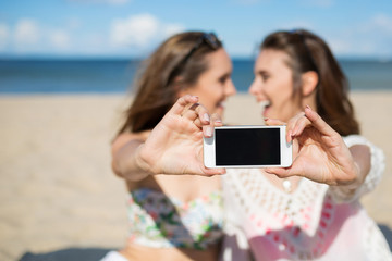 Two happy girls sitting on beach taking selfie laughing