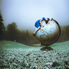 Digitally generated image of woman lying on globe