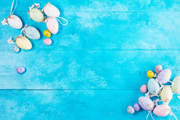 Easter eggs top view frame on bright blue background